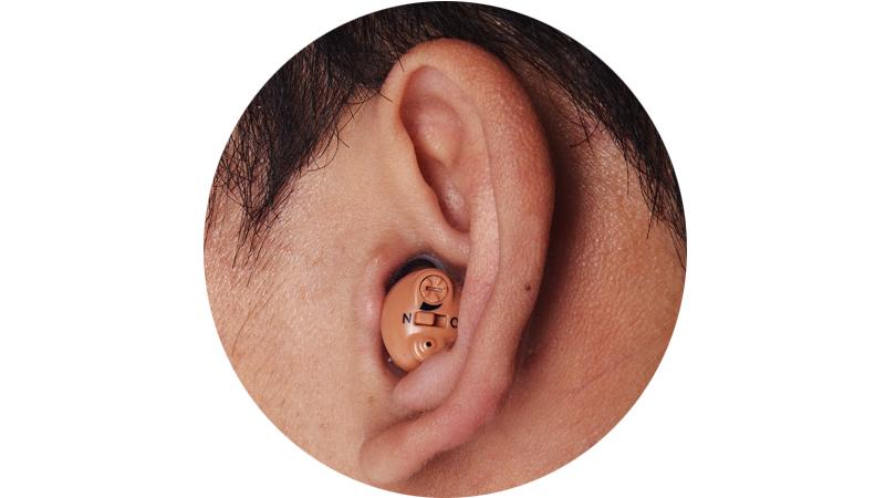 Pequeños audífonos recargables en el oído